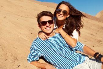 romantic-couple-with-sunglasses-lying-sand_1140-420